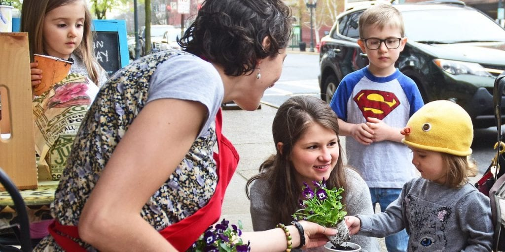 Mohawk Harvest Manager Gianna DeLilli, left, gives Hazel Hopkins of Gloversville a flower to plant as, from far left, her sister Avonlea Hopkins, her mom Ashley Hopkins and brother Christofer Hopkins, all of Gloversville look on during the 100in1 Day in Gloversville on May 4. Bill Trojan/For the Express