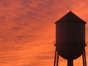 Water tower lit by Orange sunset