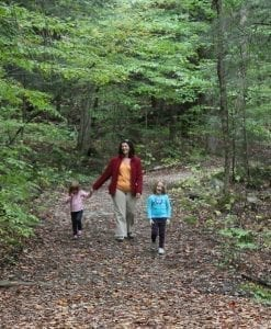 mom and children hiking on wooded trail