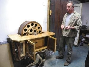 Northville artist Bill Coffey displays a spinning wine rack he is working on for a client Friday at the William Coffey Studio & Gallery in the village of Northville.