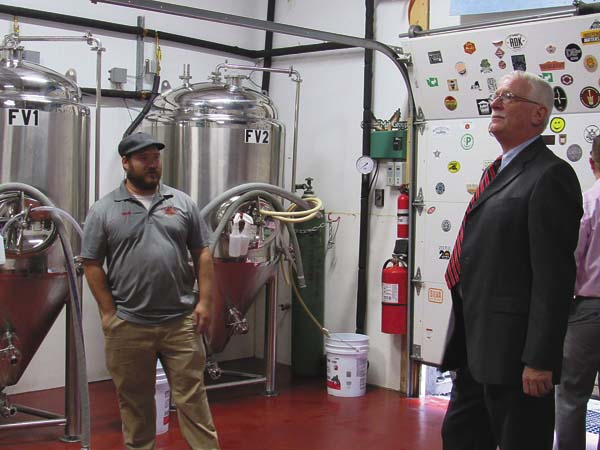 Nicholas Sherman, left, shows off some of Stump City Brewery's new equipment while giving a tour of his business for community leaders during the Fulton County Center for Regional Growth's monthly business tour on Friday.  (The Leader-Herald/Ashley Onyon)