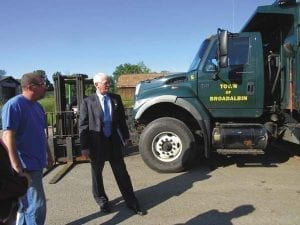 Ryan Sowle, left, shows Fulton County Center for Regional Growth President and CEO Ronald Peters a truck owned by the town of Broadalbin that the company is repairing