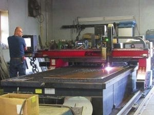 An employee at Broadalbin Manufacturing Corp. uses a hi-definition plasma cutter to cut a piece of metal at the machine shop